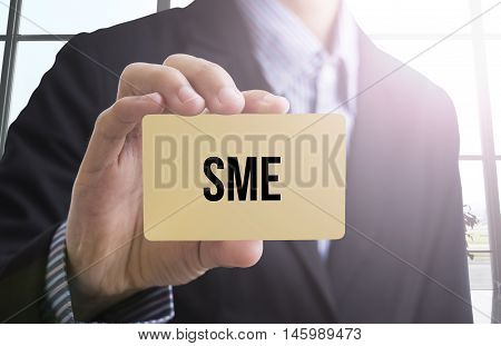 businessman hand holding a business card with a message SME small business for advertise concept.