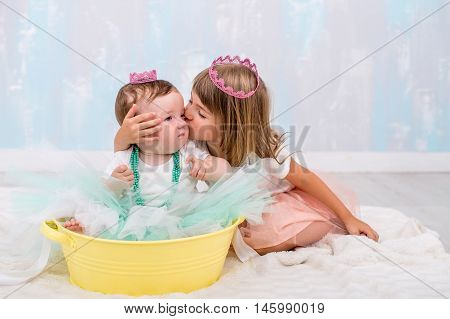 4-5 years older sister kissing younger sister 9 months on cheek. A sweet girl with pink princess crown on her head