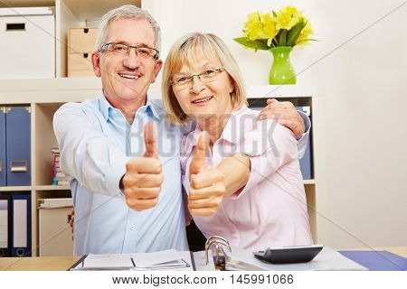 Successful senior couple smiling and holding thumbs up at their desk