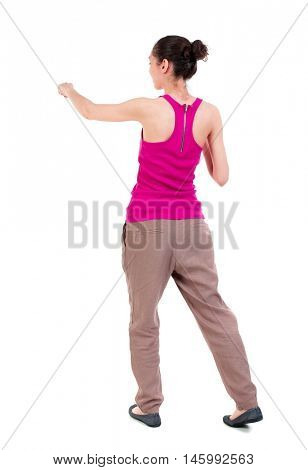 back view of woman funny fights waving his arms and legs. Isolated over white background. dark-skinned girl in a red t-shirt boxing.