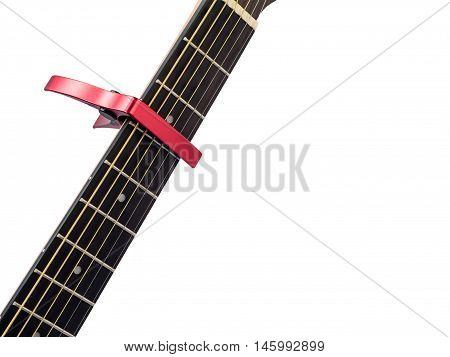 Red capo on guitar fingerboard white background close up