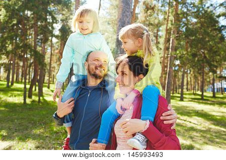 Family enjoying time together in park on warm sunny autumn day, mother and father carrying two happy girls on shoulders and talking during relaxing walk in nature