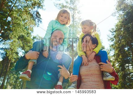 Happy family of four walking in park, mother and father carrying two cute girls on shoulders at stroll around park on bright sunny weekend in autumn, spending time together