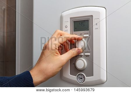 Men hand regulate temperature on 45 degree in control panel of central heating.
