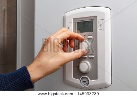 Men hand regulate temperature on 55 degree in control panel of central heating.
