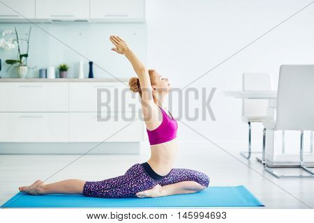 Healthy strong red haired woman doing yoga exercises at home, stretching sitting in kapotasana pigeon pose and breathing in deeply with eyes closed, ridding of all stress in life