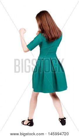 skinny woman funny fights waving his arms and legs. slender brunette in a green short dress has her hands.