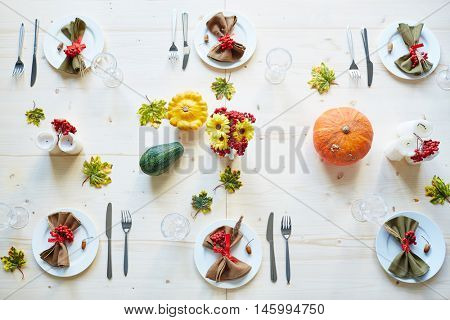 Top view of delicately decorated dinner table ready for thanksgiving party, with colorful pumpkins, rowanberry branches, maple leaves, candles and flowers on it