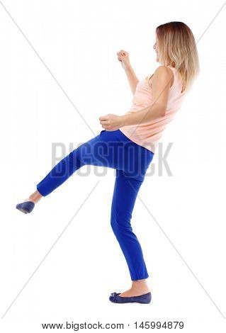 back view of standing girl pulling a rope from the top or cling to something. Isolated over white background. The blonde in a pink t-shirt has a foot.