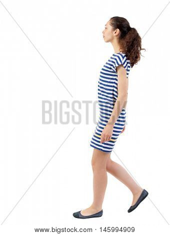 back view of walking curly woman. Swarthy girl in a checkered dress goes on the side.