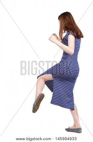 skinny woman funny fights waving his arms and legs. brunette in a blue striped dress fighting and kicking.