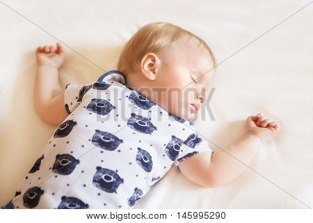 Peaceful adorable baby sleeping on his bed with white sheet in a room. Soft focus. Sleeping baby concept. 1 year-old babyboy in pajamas sleeps at home