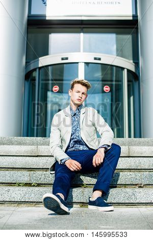 Elegant young handsome man wearing  white jacket and jeans  sitting on stairs near building
