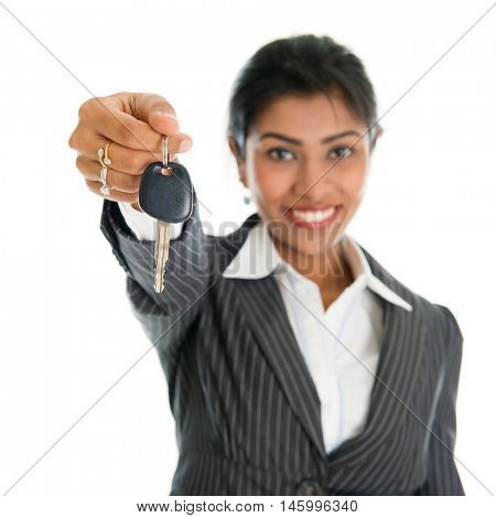 Indian woman showing car key and smiling, focus on key, isolated on white background.