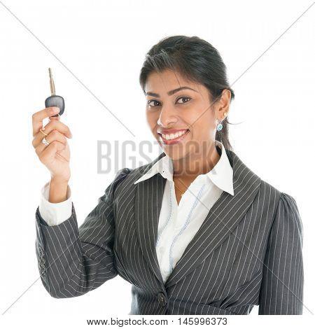 Female Indian car dealer showing vehicle key and smiling, isolated on white background.