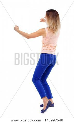 back view of standing girl pulling a rope from the top or cling to something. Isolated over white background. The blonde in a pink t-shirt fighting.