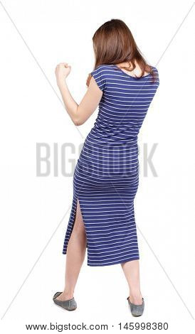 skinny woman funny fights waving his arms and legs. brunette in a blue striped dress stands sideways and fighting with their fists.
