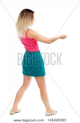 back view of standing girl pulling a rope from the top or cling to something. girl watching. Blonde in a red sweater and green skirt pulls the load on the rope.