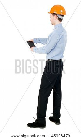 Backview of business man in construction helmet stands and enjoys tablet or using a mobile phone. Curly businessman in a light jacket and a helmet holding a tablet vertically.