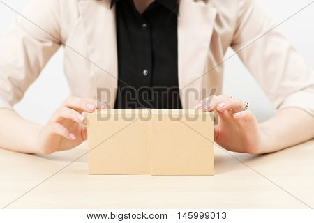 Unrecognizable woman showing boxes with pkg, copy space. Female hands holding two parcels with free space, great background for advertisement any product. Goods packaging, online shopping concept