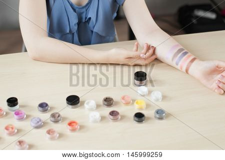 Make up artist testing eyeshadow colors. Woman stylist trying cosmetics color on her hand, doing swatches. Professional coloring, visagiste, beauty concept