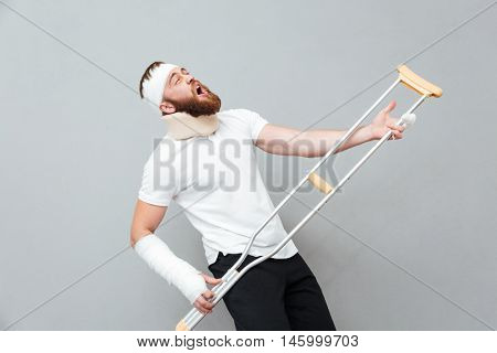 Happy funny young man singing and having fun with crutch over white background
