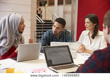 Group Of Students Meeting For Tutorial With Teacher