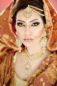 Portrait of a pretty girl in traditional Indian Pakistani bridalwear with heavy jewelry and makeup poster