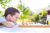 young chess player outdoors. the boy concentrating on the game of chess. view profile poster