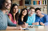 Happy group of young students studying together in a college library and looking at camera smiling poster