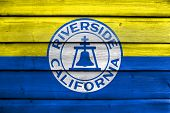 Flag of Riverside California USA painted on old wood plank background poster