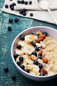 Bowl of oatmeal porridge with banana, blueberries, almonds, coconut and caramel sauce on teal vintage table. Hot and healthy food for Breakfast. poster