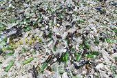 Glass waste for recycling in a recycling facility. Different glass packaging bottle waste. Glass waste management. Process of waste glass into usable products. Pile of different bottles. poster