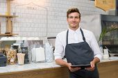 Successful small business owner holding digital tablet and looking at camera. Happy smiling waiter with apron and digital tablet leaning on counter. Portrait of young entrepreneur of coffee shop. poster