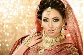 Pretty girl in traditional Indian Pakistani bridal costume with heavy makeup and jewellery against a glittery background poster