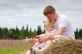 Father And Daughter Have Fun With Toy Aircraft Model On Haystack