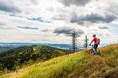 Mountain biker riding on bike in summer inspirational mountains landscape. Man cycling MTB on enduro trail path. Sport fitness motivation and inspiration. Rider mountain biking in summer woods. poster