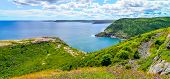 Sunny summer day over rocky coastline cliffs of Canadian National Historic site  Fort Amherst, St John's Newfoundland.  Cape Spear in background, people in distance hiking along the Cabot trail. poster