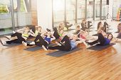 Group of young women in fitness class. Group of people making exercises. Girls do cross crunches for abs. Healthy lifestyle, training, sport, gym studio. Sporty girls in fitness club, aerobics. poster