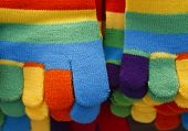 close up of knitted striped winter gloves in bright colors poster