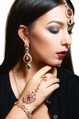 Gorgeous woman with luxurious jewelry close-up. Portrait of beautiful indian princess with ceremonial makeup and finery. Luxury, wealth, pleasure concept poster