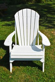 One White Adirondack Chair in a Grassy Country Setting