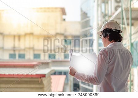 Engineer Or Architect Checking Architectural Drawing While Wearing A Personal Protective Equipment S