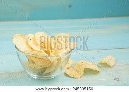 Crispy Potato Chips In Bowl On Blue Wooden Background