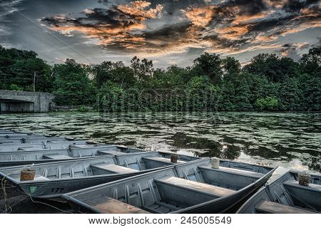 Boats In Lake Under Cloudy Sky With Wooded Background