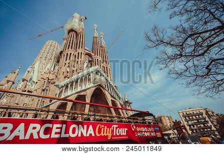 Barcelona, Spain - April 25, 2018: Barcelona City Tour Touristic Bus In Front Of Famous Sagrada Fami