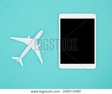 Miniature Toy Airplane And Tablet On Pastel Blue Background, Flat Lay Design Of Travel Concept With