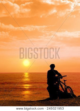 Boy With His Bicycle Resting And Looking At The Sea. Silhouette Boy With His Bicycle During Sunset.