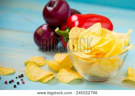 Crispy Potato Chips In A Glass Bowl With Paprika And Onions On Old Blue Wooden Background. Potato Ch