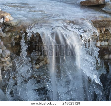 Rocky Cascade With Ice All Over And Water Running Underneath
